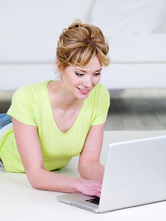 Beautiful young smiling woman in casuals lying and using laptop - indoors photo