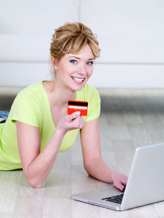 Beautiful blonde woman with happy smile holding credit card and using laptop - indoors photo