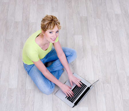 high angle: Happy woman  sitting on the floor with laptop - high angle view Stock Photo