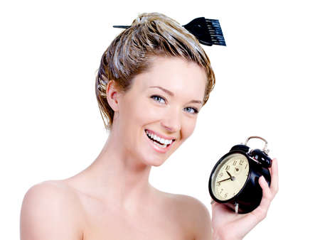 hair brush: Portrait of beautiful woman with dye on a hair and holding clock - isolated on white