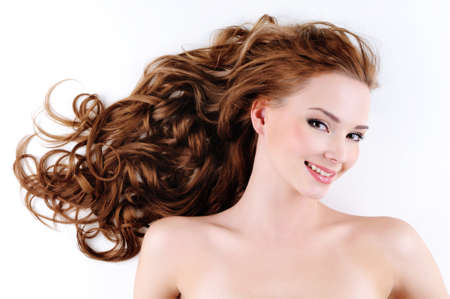 curly hair woman: Portrait of the happy beautiful  woman with brown long ringlets hair Stock Photo