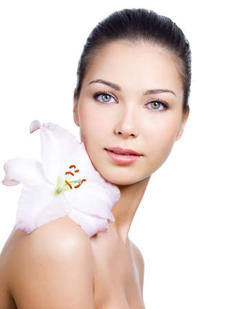 Close-up portrait of young beautiful face of woman with clean skin and flower on a shoulder - white background Stock Photo - 7337573