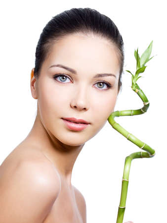nude young: Close-up portrait of young beautiful face of woman with clean skin and with plant - white background
