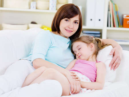 Beautiful happy young mother with little sleeping daughter on a sofa at home photo