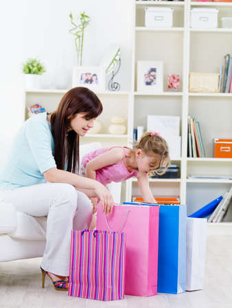 Young mother with little curiosity faughter opening purchase after shopping at home photo