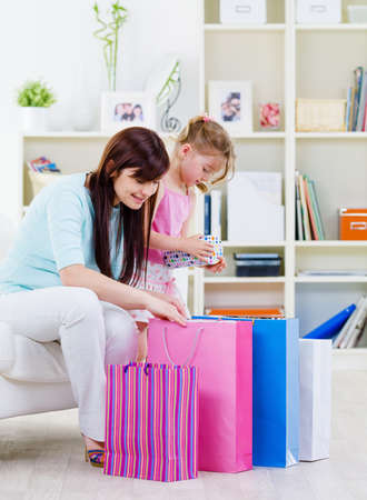 Young mother with little daughter at home with purchases - indoors photo