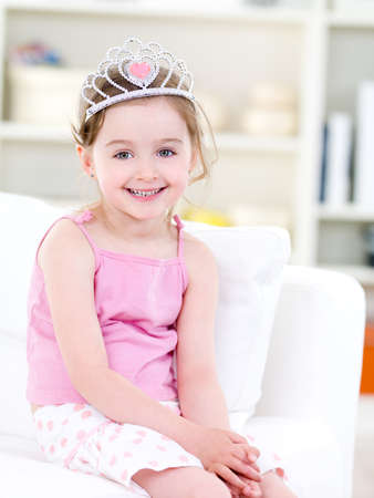 Beutiful pretty little girl with happy smile sitting on the sofa with crown - indoors photo