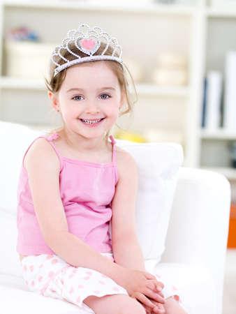 ni�os contentos: Preciosa bastante peque�a ni�a con sonrisa feliz sentado en el sof� con corona - en el interior