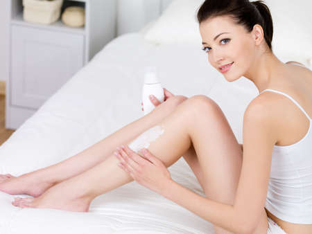 woman legs: Young beautiful woman applying body lotion on her attractive legs - indoors Stock Photo