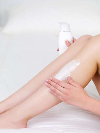 Applying lotion on a beautiful womans legs - indoors photo