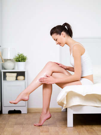 apply: Caring about womans leg with moisturizing cream by young beautiful woman sitting on a bed at home