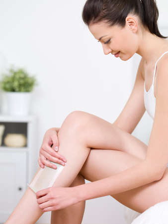 Portrait of beautiful young smiling woman in profile depilating her legs by waxing - indoors photo
