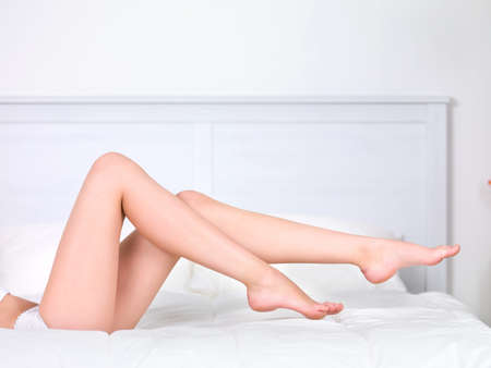 woman's: Beautiful womans perfect clean legs on the bed - indoors