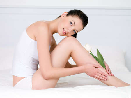 woman legs: Beautiful young woman with white tulip on her attractive perfect legs - indoors