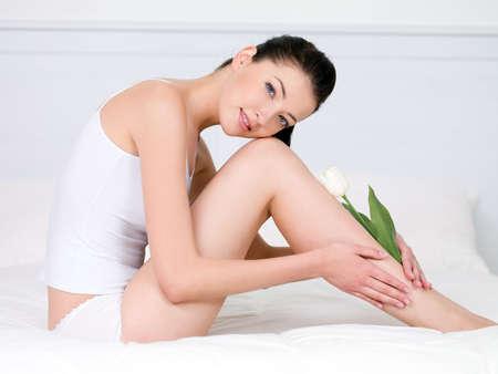 benen: Mooie jonge vrouw met witte tulip op haar aantrekkelijke perfecte benen - binnenshuis Stockfoto