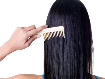 Combing healthy long straight female hair - close-up