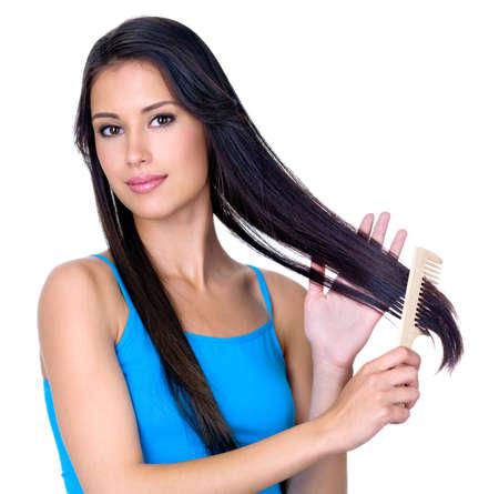 Giovane donna bruna piuttosto pettinatura dei suoi lunghi capelli belli - isoalted su sfondo bianco