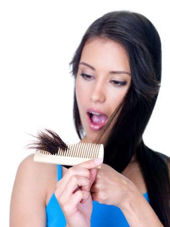 peigne: Horreur sur la face de la jeune femme regarde les extr�mit�s malsaines de cheveux - isol�