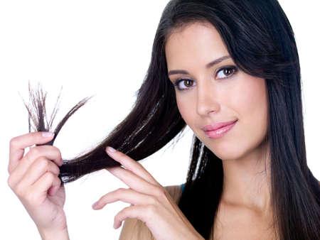 groviglio: Ritratto di sorridente giovane donna bella azienda le estremit� del suo sfondo lunghi capelli castani - bianco