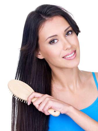 peine: Sonriente joven y bella mujer pein�ndose su cabello largo casta�o con cepillo - aislado