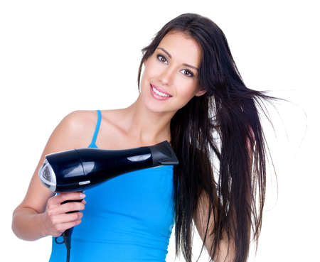 Beautiful smiling young woman drying her hair with hairdryer - isolated on white photo