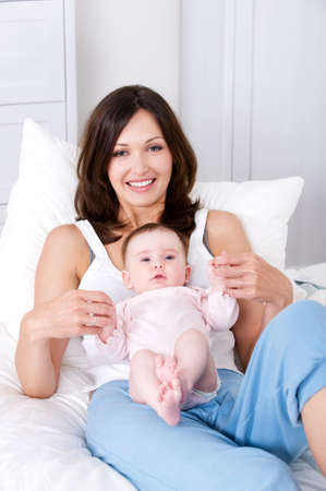 casuals: Beautiful young mother sitting in casuals with little newborn baby at home Stock Photo