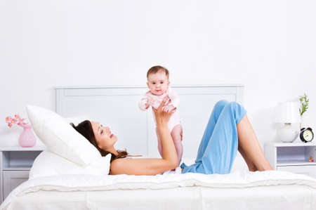 Mother lying on a bed and playing with newborn baby - indoors photo