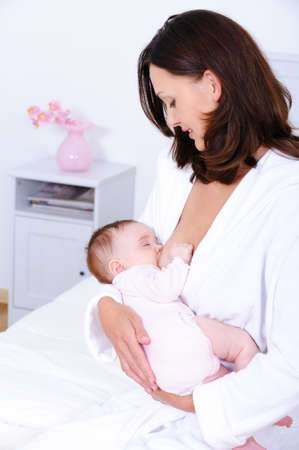 Portrait of young mother feeding her newborn baby with breast - indoors Stock Photo - 7378371