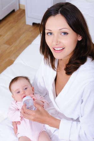 dentudo: Retrato de alto �ngulo de feliz madre de joven hermosa con sonrisa pez alimentando a su beb� con biber�n - en el interior