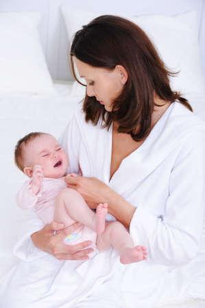 bebe enfermo: Retrato de mujer hermosa cuidado sobre su peque�o beb� - en el interior  Foto de archivo