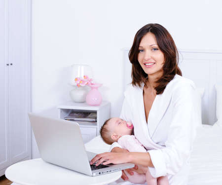 Happy beautiful young mother sitting with baby and with laptop at home - indoors photo