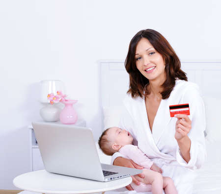 Beautiful young mother sitting with baby, holding credit card and using laptop - indoors photo