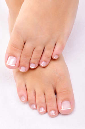 Beautiful female feet with the French pedicure on a white towel photo