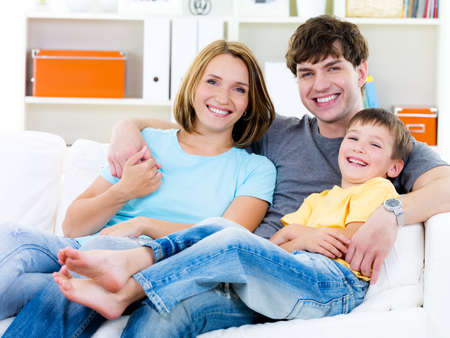 family on couch: Beautiful young happy family with son sitting on the sofa - indoors Stock Photo