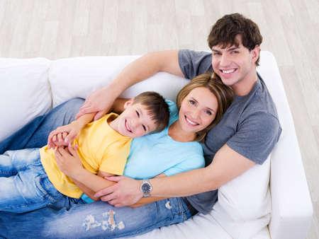 familia abrazo: Amistosa familia riendo feliz en el sof� - �ngulo alto