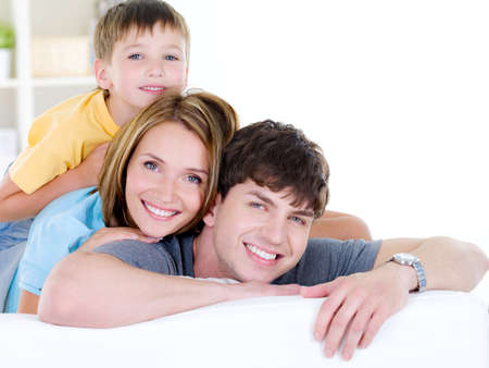 Beautiful happy smiling family of three people with young son - indoors Stock Photo - 7378449