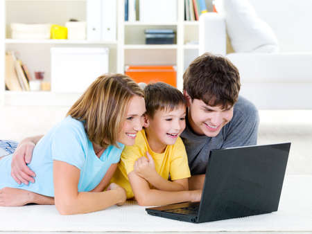 internet love: Beautiful happy family with child looking at laptop with cheerful smile - indoors Stock Photo