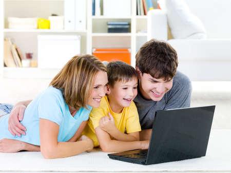 Hermosa familia feliz con niño mirando portátil con alegre sonrisa - en el interior
