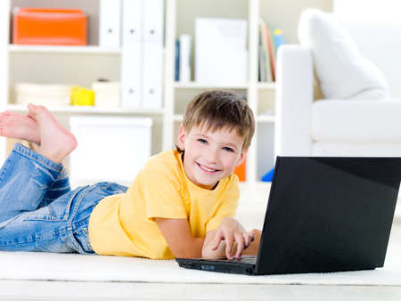 10s: Happy little boy with laptop lying on the floor at home - indoors