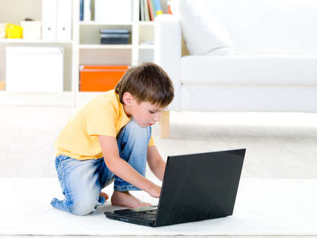 10s: Little child in casuals playing on laptop at home - indoors