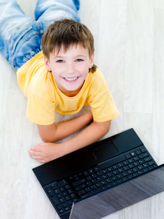 10s: High angle portrait of little happy cheerful boy with laptop on the floor Stock Photo