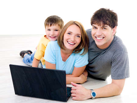Three happy laughing people with little boy on the floor with laptop - indoors photo