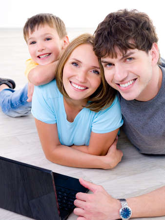 Portrait of happy laughing young family with little son and with laptop - indoors photo