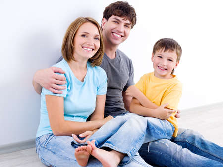 casuals: Happy beautiful young family in casuals sitting on the floor - indoors