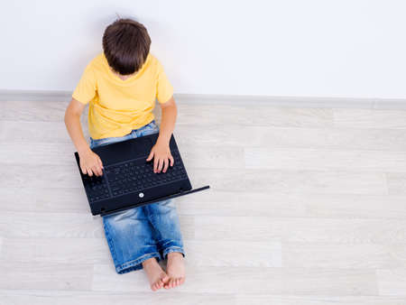 High angle shoot of little boy using laptop - indoors photo