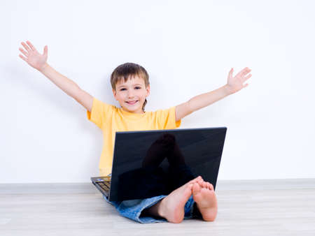 10s: Happy little boy with laptop with moving apart his hands - indoors