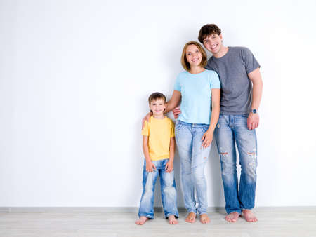 casuals: Happy young family with little son standing together in casuals near the empty wall - indoors