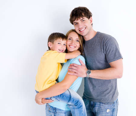 bonding: Beautiful young happy family in emrace with little son - indoors Stock Photo