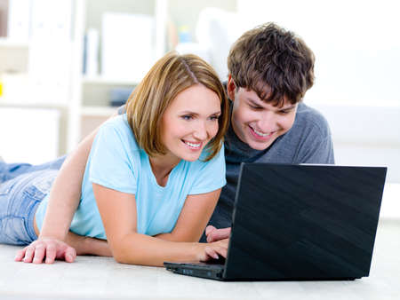 Happy smiling couple of people looking at laptop with interest - indoors Stock Photo - 7416202