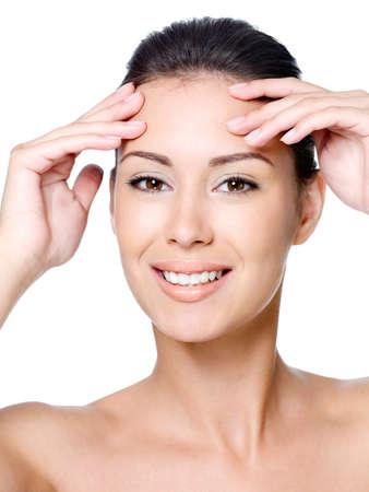 rides: Femme belle jeune souriante heureuse toucher son front sans rides - gros plan